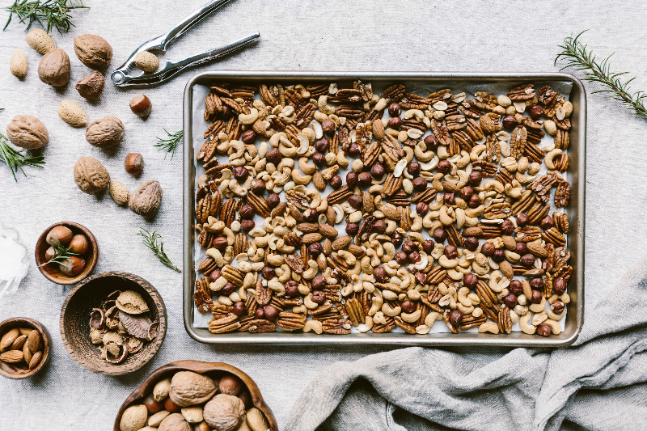 a few cups of mixed nuts are placed on a rimmed baking sheet to be toasted in the oven.