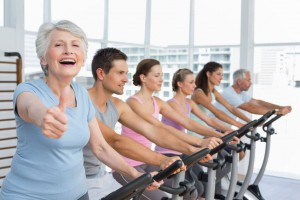 Woman gesturing thumbs up with class working out in the gym