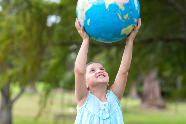 little girl holding a globe on a sunny day