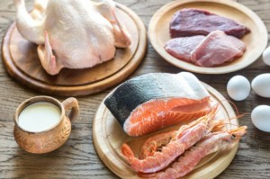 Meat, poultry, fish and shellfish in plates on a table
