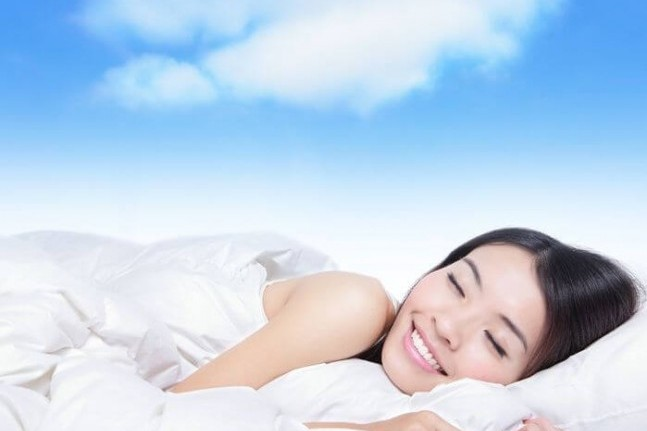 young girl sleeping on a pillow with white cloud over her