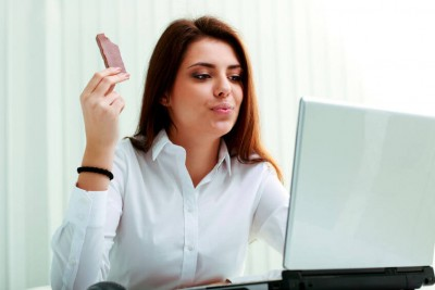woman eating chocolate while working on the computer