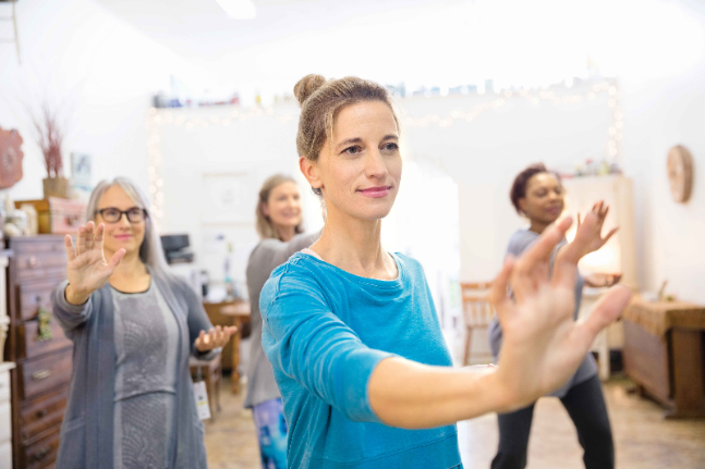 Women practicing tai chi in exercise class