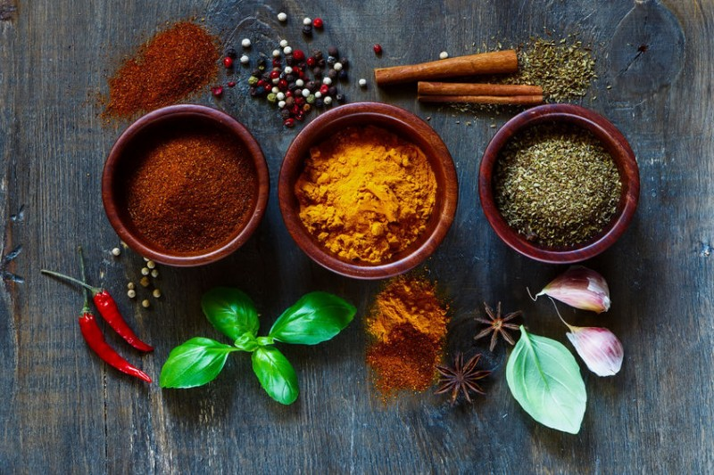 Assorted spices and herbs over dark old wood