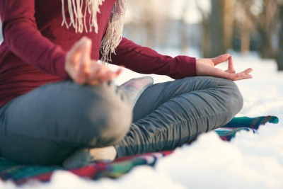 woman practising meditation on a blanket- practiced mindfulness