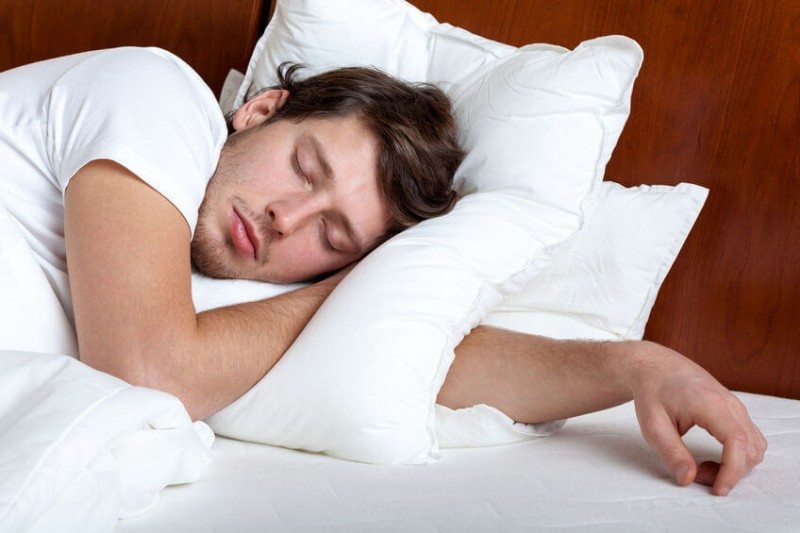 Young man sleeping in his bed on white pillow