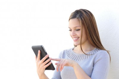 Happy woman texting on her tablet against a white background