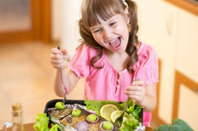 young child girl holding a fork and knife over a fish dish