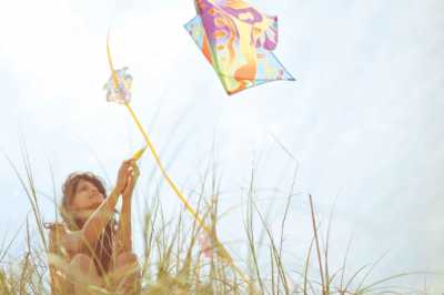 A beautiful Indian woman flying a kite from the top of a hill on a beautiful summery day at the beach in North carolina.