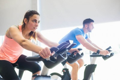 man and woman exercising on bikes in a gym