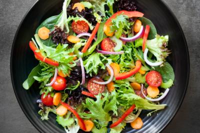 62552812 - garden salad in black bowl. top view, over slate.