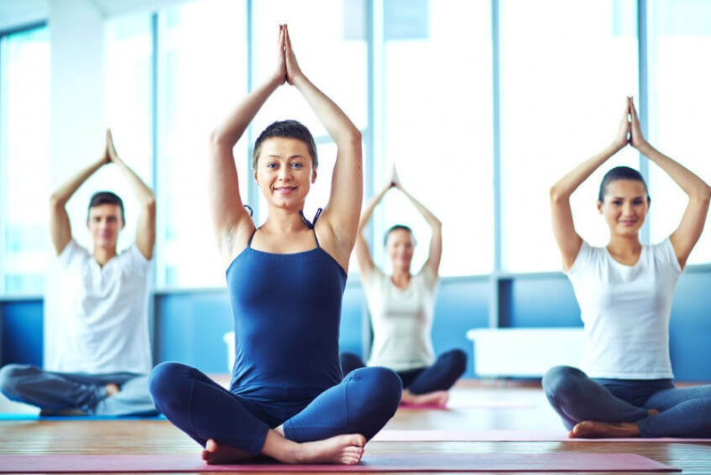 Young woman practicing yoga in yoga class