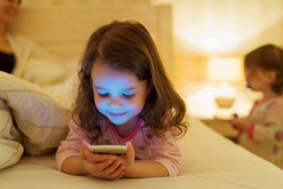 little girl using a smartphone in bed at bedtime