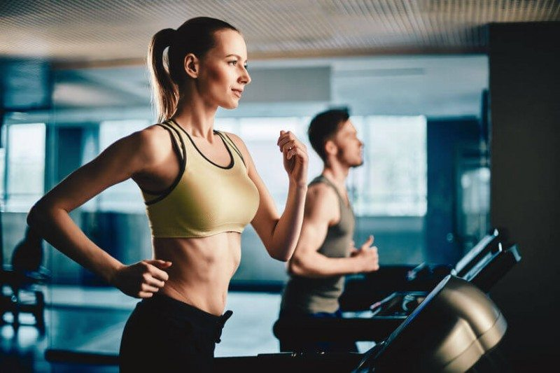 woman and a young man exercising on the treadmill