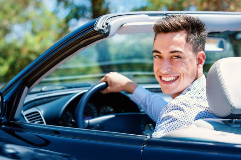 Young man sitting in convertible in driver seat.