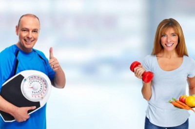 Happy man with a weight scale and female partner holding weights and a plate of raw vegetables and fruits
