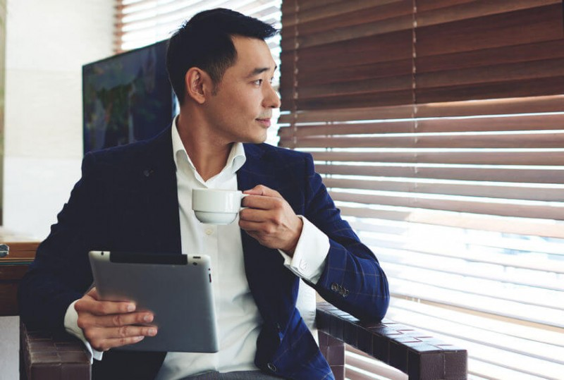 young confident businessman enjoying coffee while work on his digital tablet