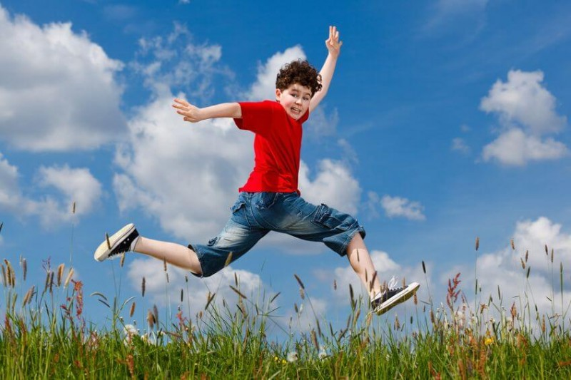 young boy running jumping in a field against a blue sky