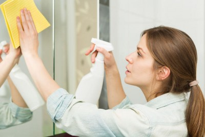 clean: woman cleaning mirror with a spray and cloth