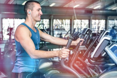 Smiling muscular man using elliptical machine at gym