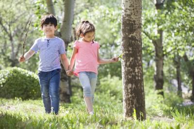 Happy children holding hands walking in green spaces