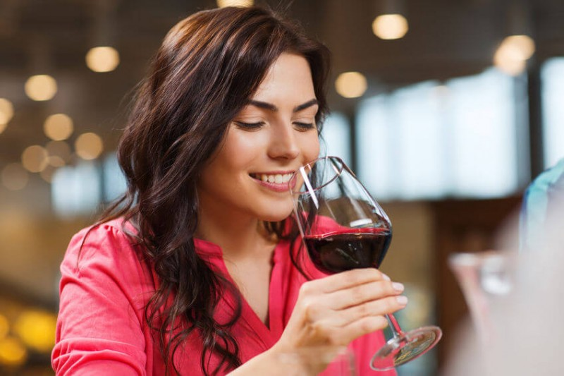 woman smiling with a glass of red wine in hand