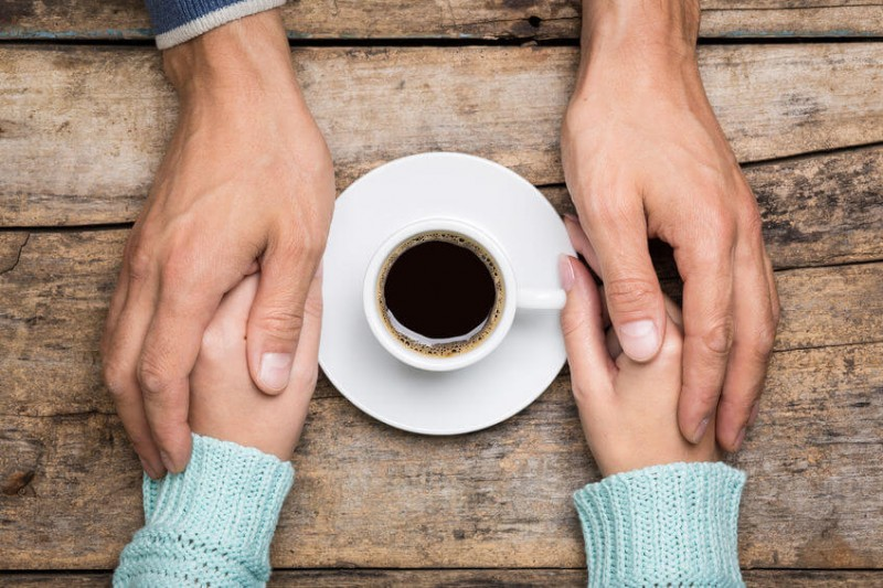an holds woman's hand near a cup of coffee top view image