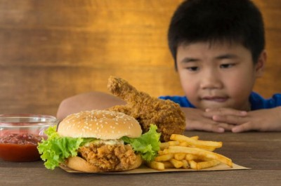 hungry child staring at a burger and fries on a wooden table