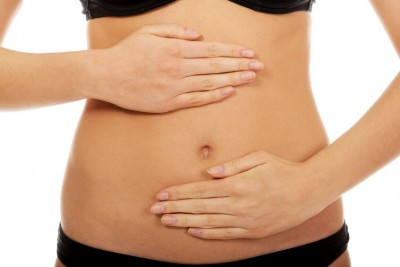 Young woman touching her belly due to autoimmune response