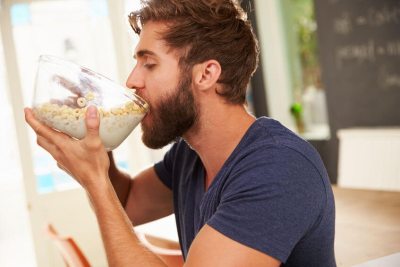 hungry man eating cereal from a glass bowl