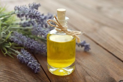 Essential lavender oil with fresh flowers on wooden background