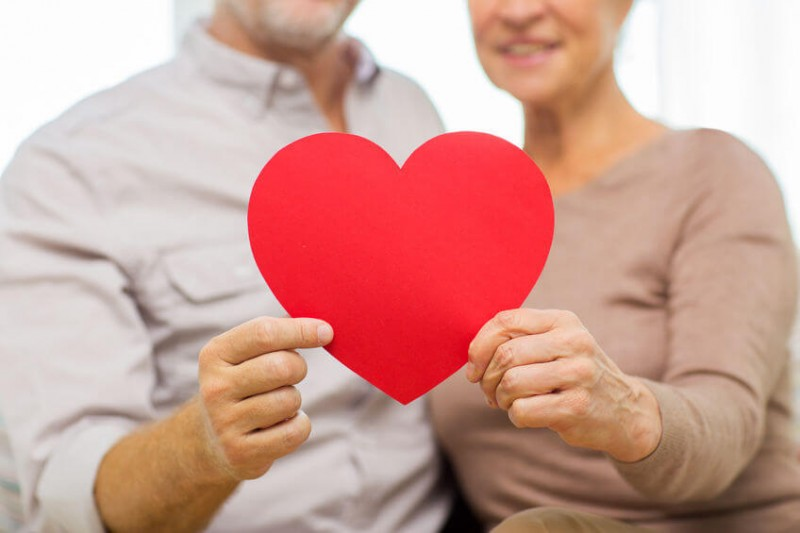 happy senior couple holding up a red paper heart