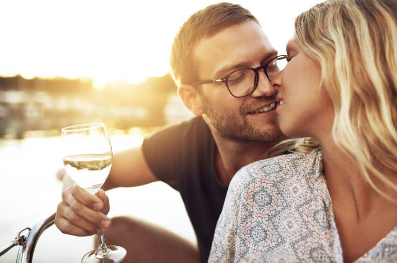 Couple Kissing Gently while Enjoying a glass of Wine