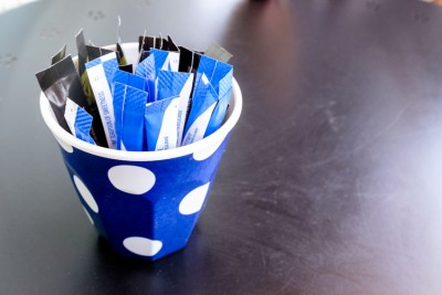 lue and white paper sachets of artificial sweetener in a blue and white spotted cup on a table.