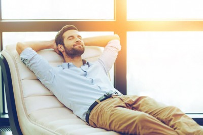 man relaxing on the couch with eyes closed