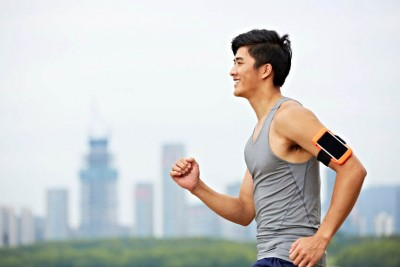 male jogger with fitness tracker attached to arm running