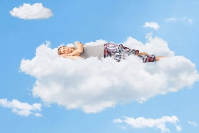 young woman dreaming and sleeping on a cloud