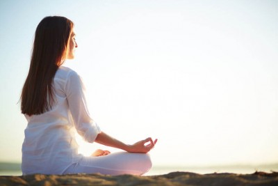 side veiw of a woman meditating oudoors