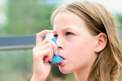 Girl having asthma using asthma inhaler