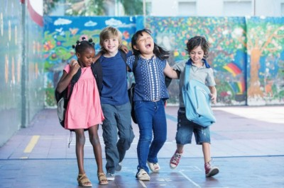Happy kids embracing and smiling in the elementary schoolyard