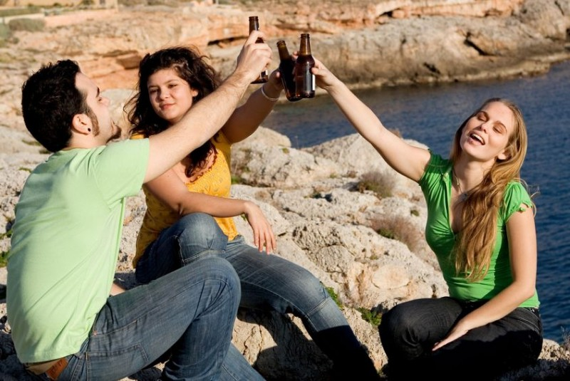 young people drinking sitting on rocks