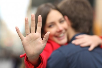 woman looking at her engagement ring on her finger while hugging her boyfriend