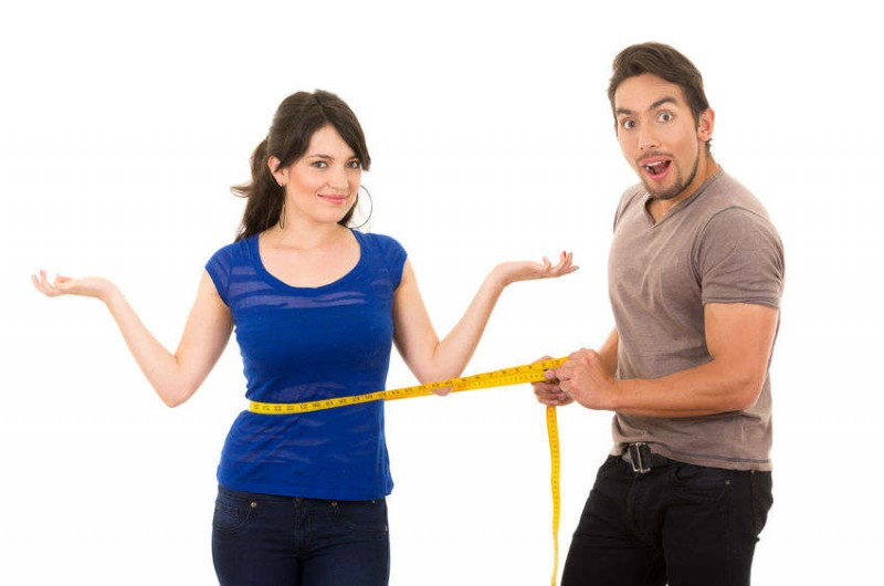 man holding a measuring tape around a womand stomach showing weight loss