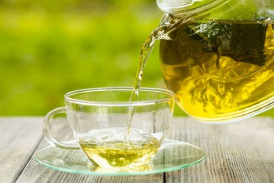 Herbal green tea in a glass teapot on the table outdoor