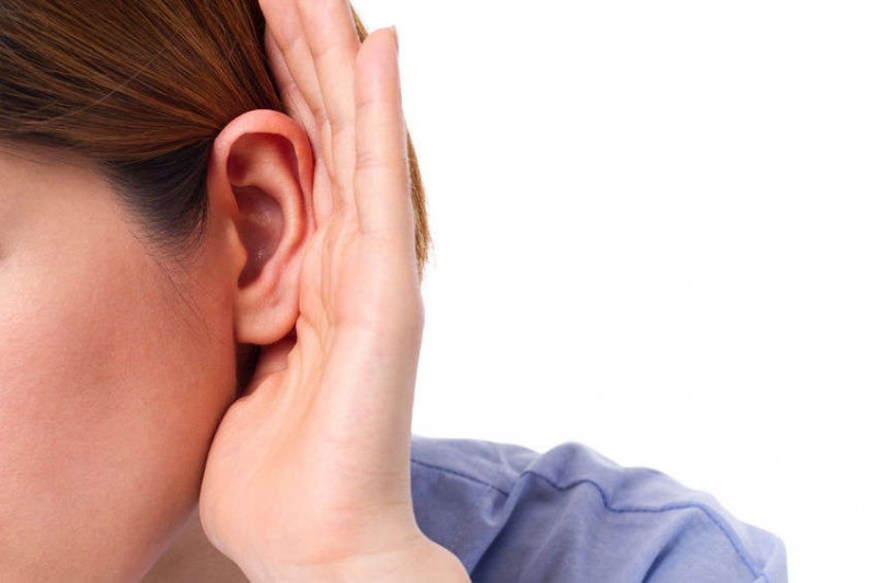 close up of woman's ear with her hand cupping it