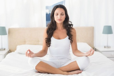 woman practising mindfulness meditation on a bed