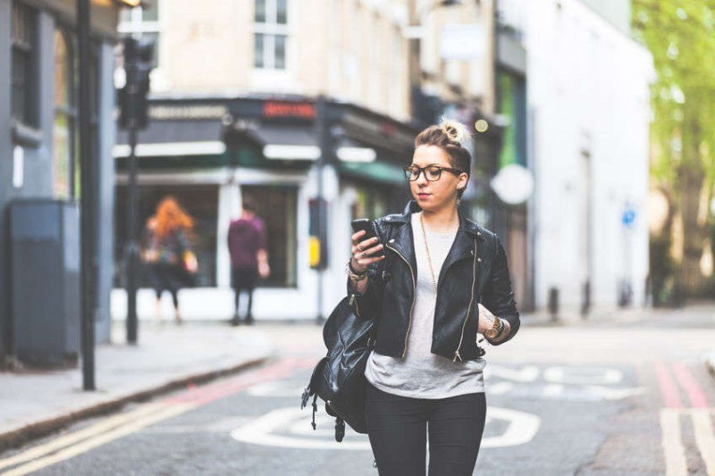 woman walking on street whicle looking at smartphone