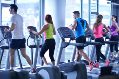 young people running on treadmills in modern sport gym