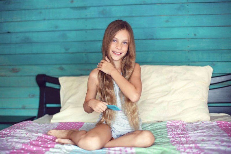 9 years old girl brushing her long hair in her bedroom