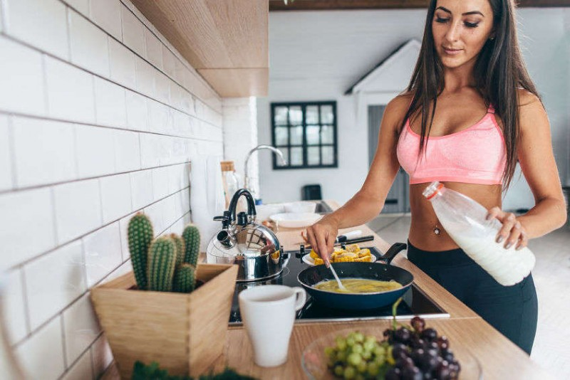 woman in fitness clothes preparing breakfast